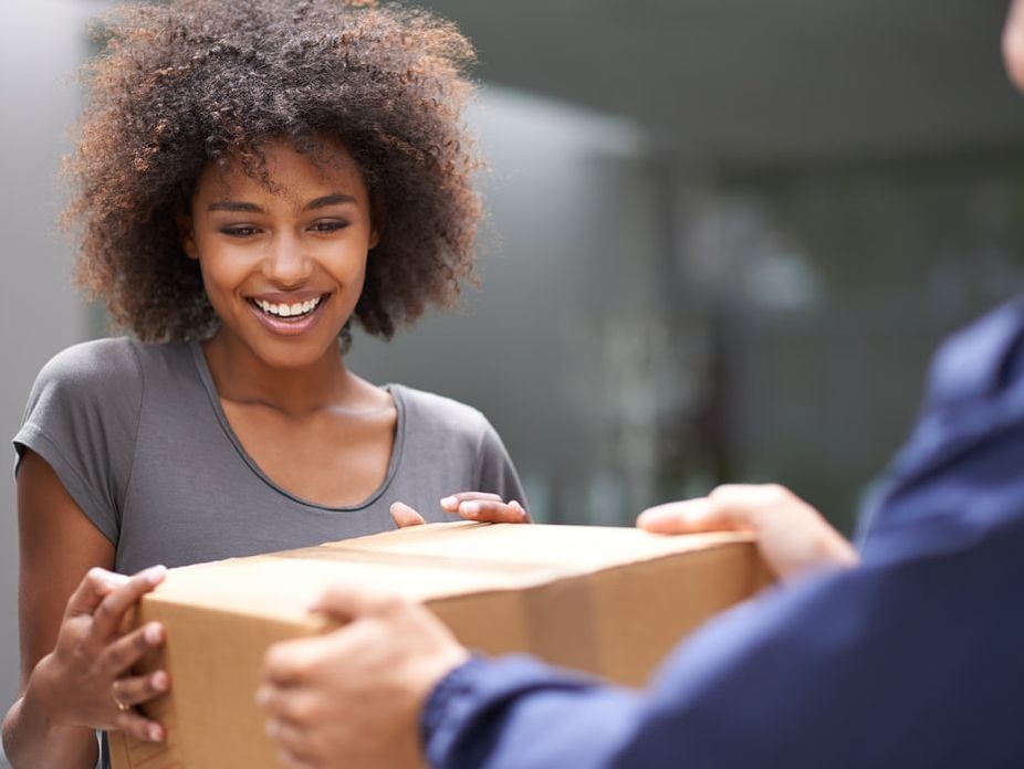 woman is handed a package by a courier
