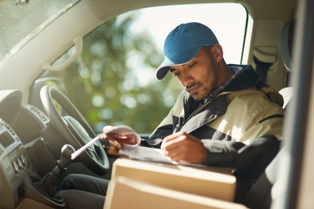 courier reviewing documents in his vehicle